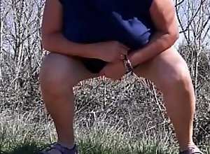 Mature woman pissing in nature