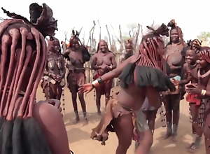 African Himba women dance and swing their saggy..
